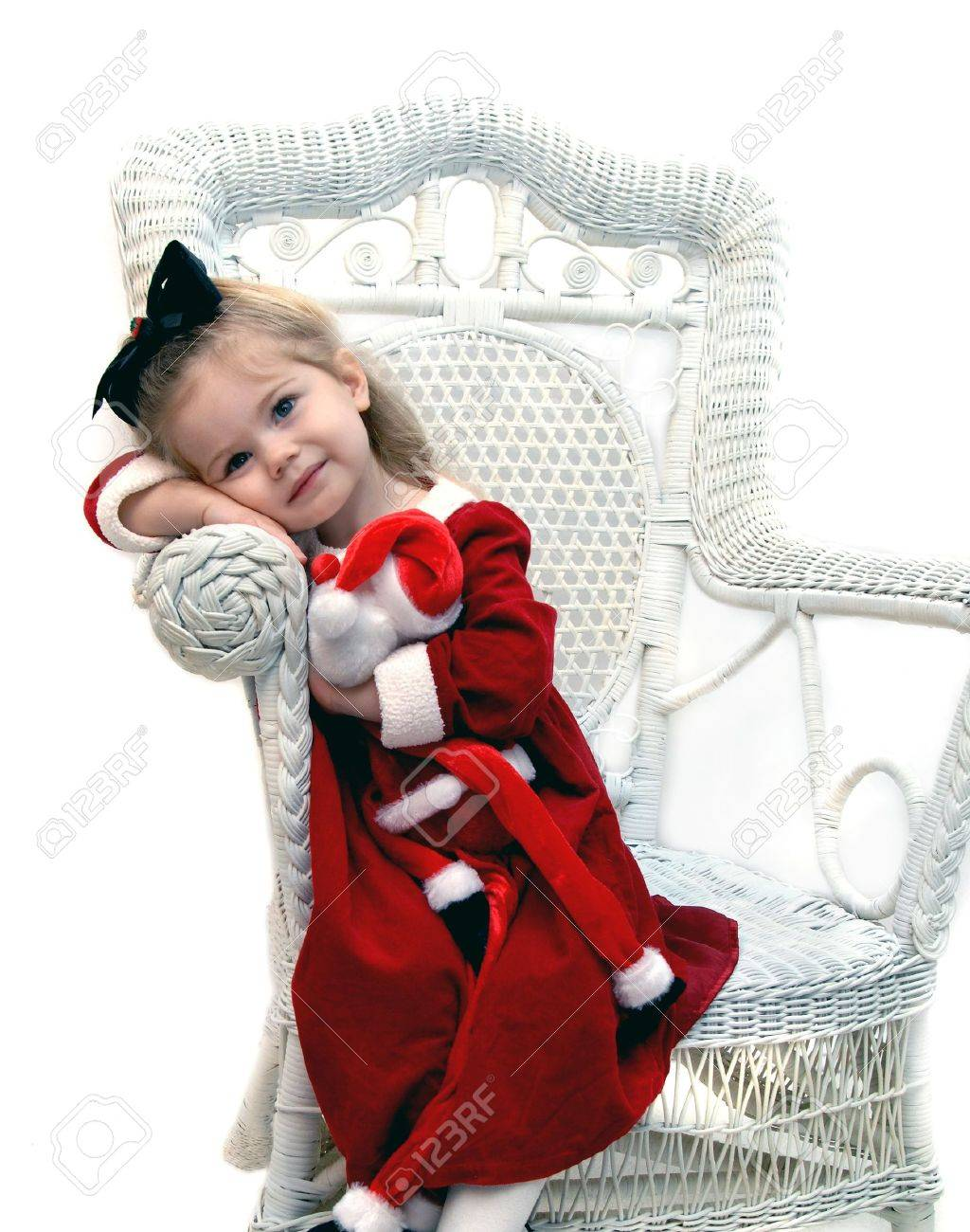 Little girl, clutching her Santa Claus doll, dreams of Christmas morning.  She is wearing a red dress and white leotards and sits in a white wicker chair. Stock Photo - 14865857