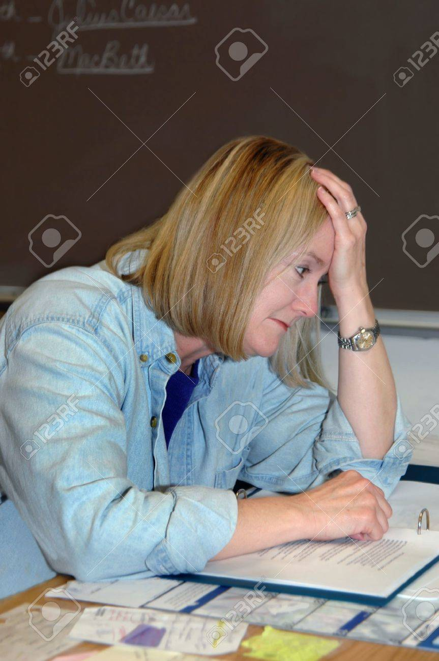 Female teacher overwhelmed with the stress of educating todays youth, leans her head in her hands and falls into negative thoughts   Blackboard and cluttered desk Stock Photo - 14913384