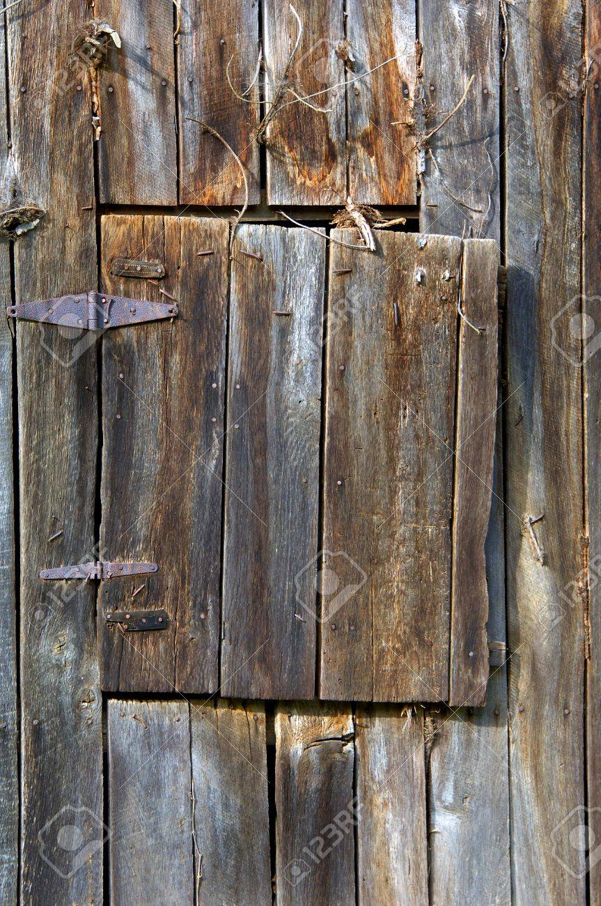 Weathered Wood Leather And Iron Hinges Hold An Aging Loft Door