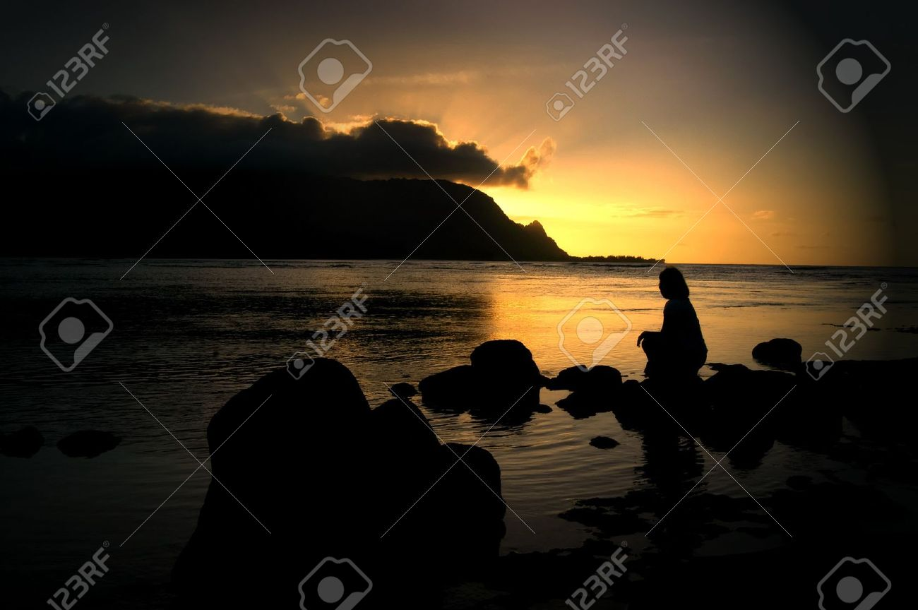 Woman sits alone on a beach at Princeville, Kauai and watches the sun set behind a bank of clouds and the Kauai mountains. Sunset tints the sky and waters a brilliant gold. - 14922799