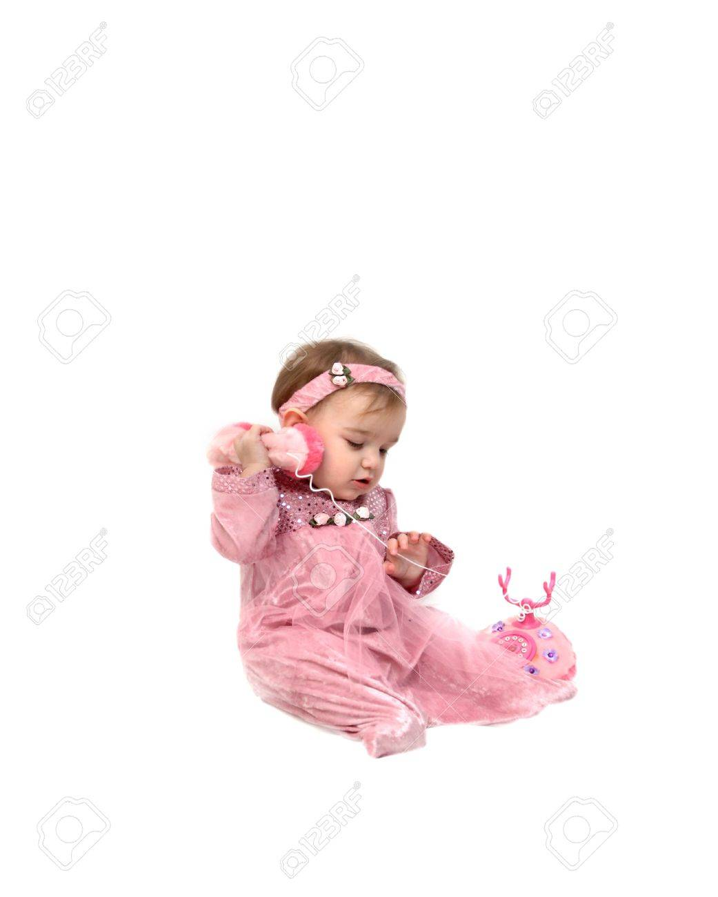Baby girl holds a play telephone to her ear.  She is wearing a pink velvet and net sleeping and answers a pink telephone. Stock Photo - 15023388