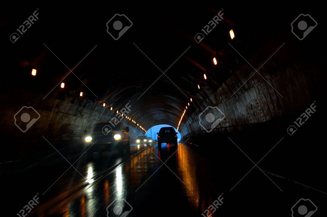 Tunnel traffic has added danger of wet roads. Headlights throw rays of light in front of truck. - 15023697