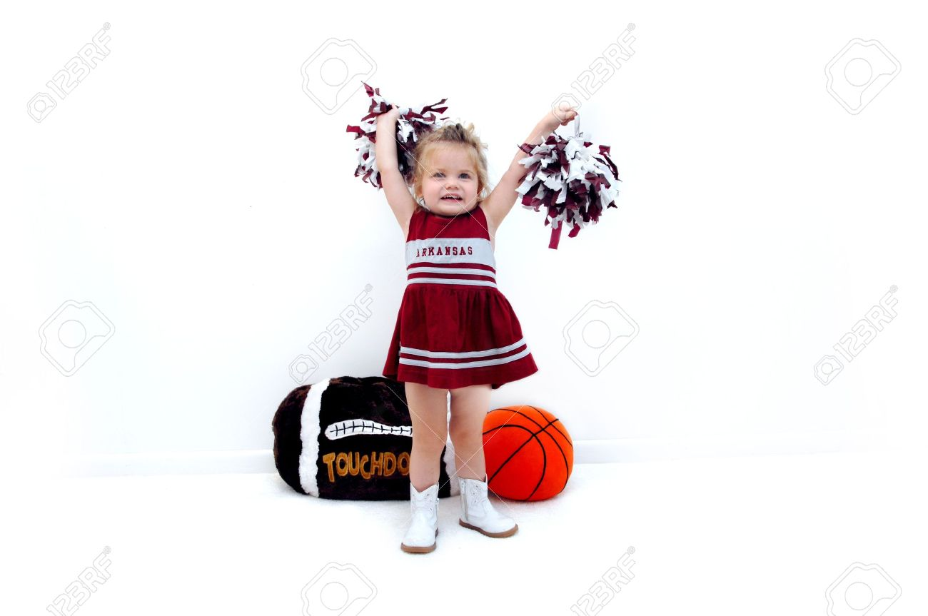 Little cheerleader dressed in burgundy and grey holds pom poms high in the air She is wearing white gogo boots and standing in front of a stuffed football and basketball - 15023628
