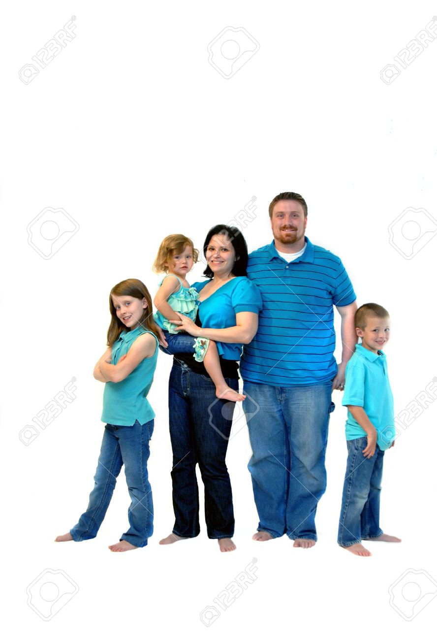 Family of five stand in jeans, aqua shirts and barefoot in a room of all white All are smiling and happy - 15045828