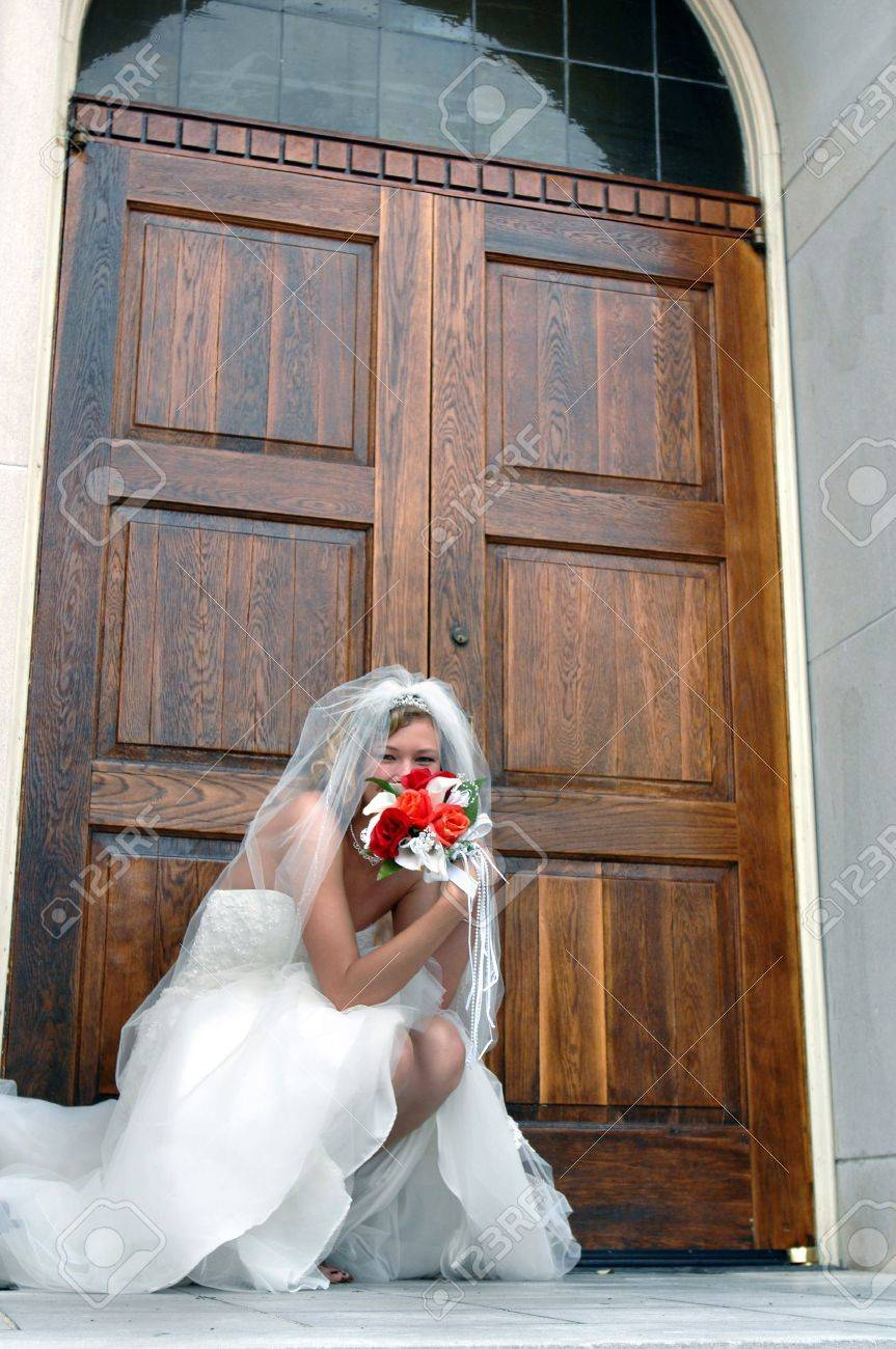 Bride kneels besides the chapel door, anticipating the doors opening for the ceremony She is teasingly hiding her face behind he bouquet of red and orange roses - 15024480