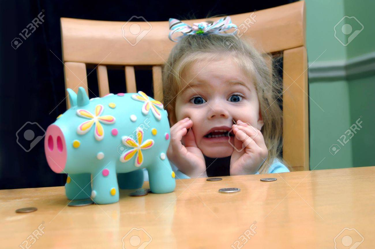 Little girl looks upset that she has to save all her pennies She is holding two against her cheek Brightly colored aqua piggy bank sits besides her at their kitchen table - 15023993