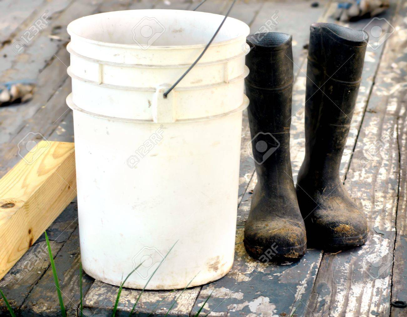 Muddy work boots set besides a five gallon bucket on a wooden porch Porch boards are cracked and peeling Work gloves lay in background Boots represent a work ethic - 15056430