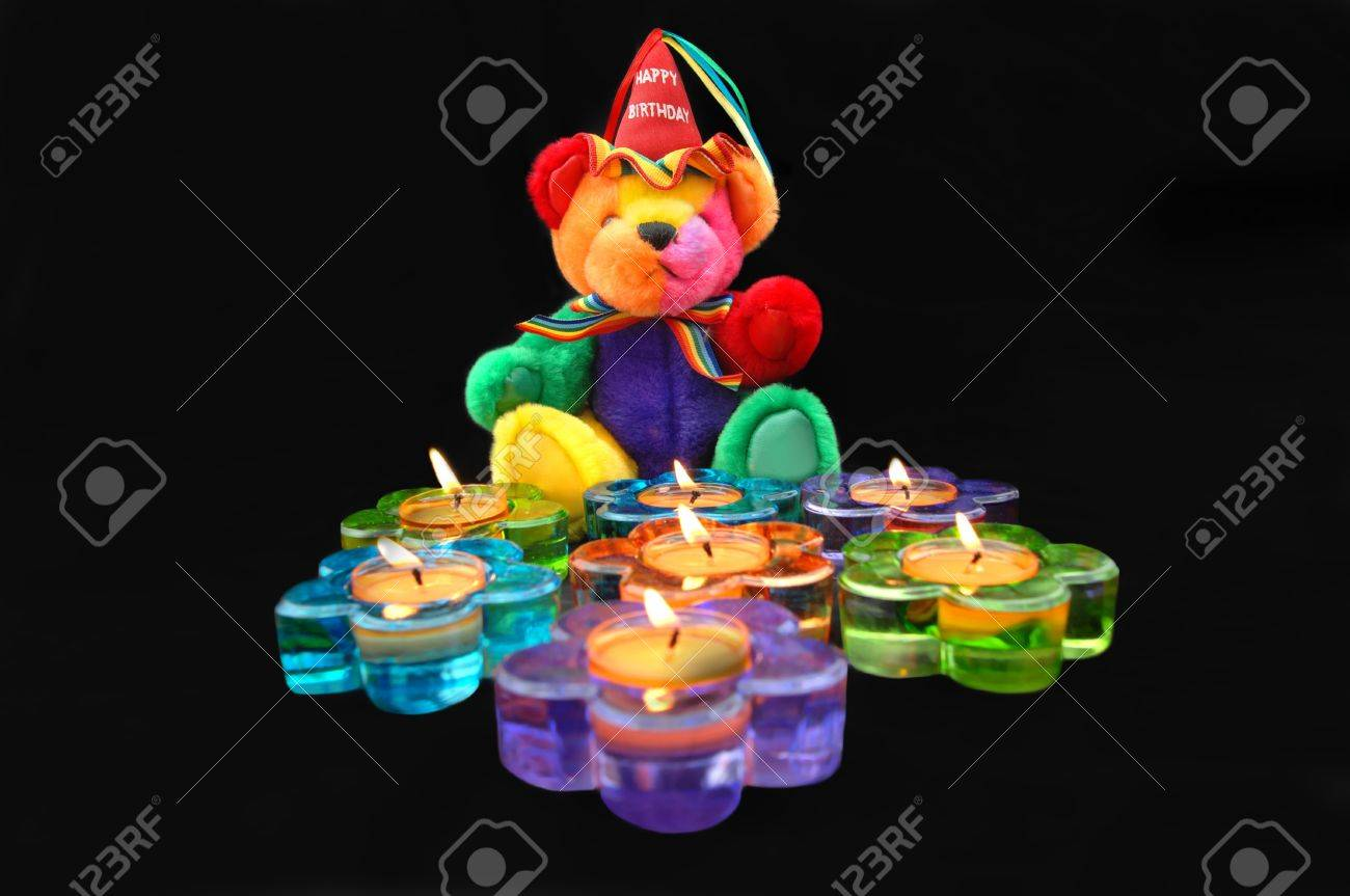 Happy Birthday Teddy Bear Sits In Front Of Flower Shaped Candles Are Burning And