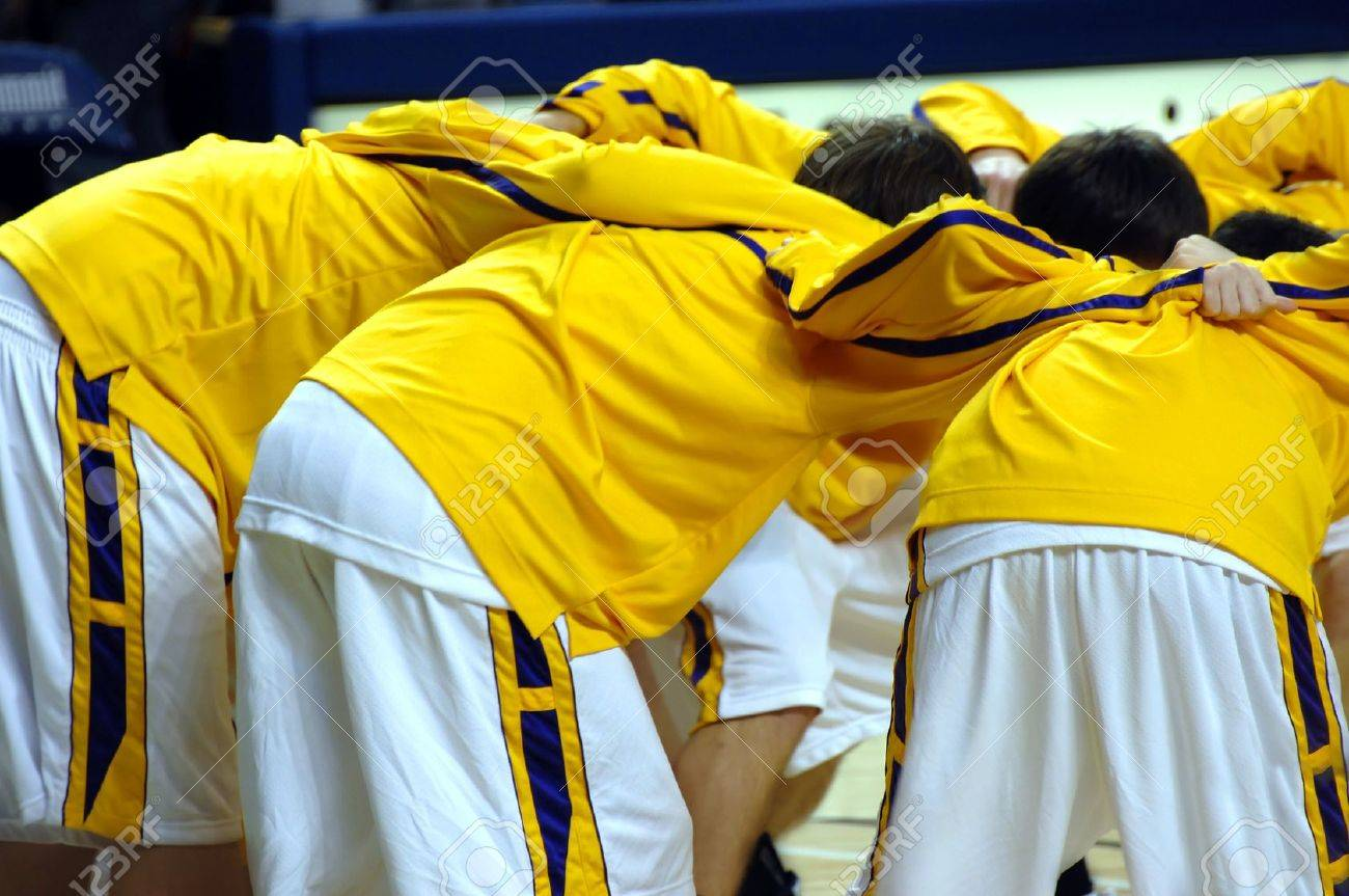 High school varsity basketball team huddles together before game start. Uniforms are yellow, purple and white. - 15057465