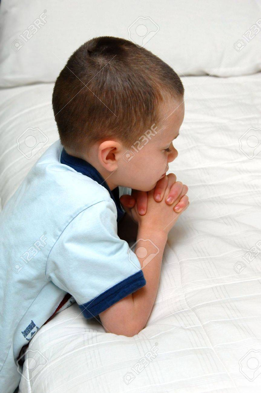 Small child kneels besides his bed and folds his hands in prayer He is wearing a blue shirt and kneeling besides a white covered bed - 15057335