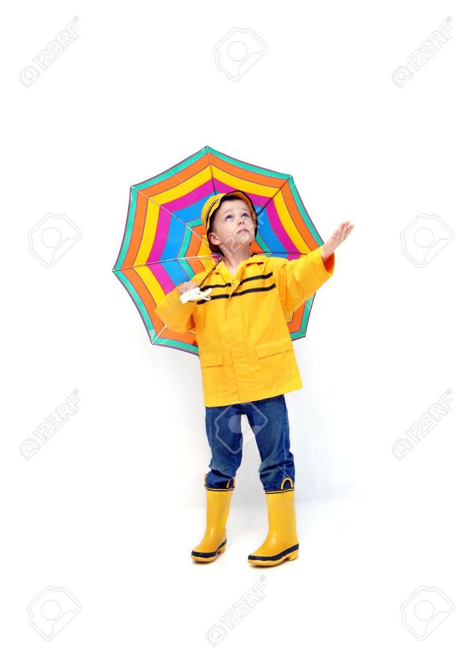 Chico joven en impermeable amarillo y botas de goma extiende la mano para  comprobar si hay