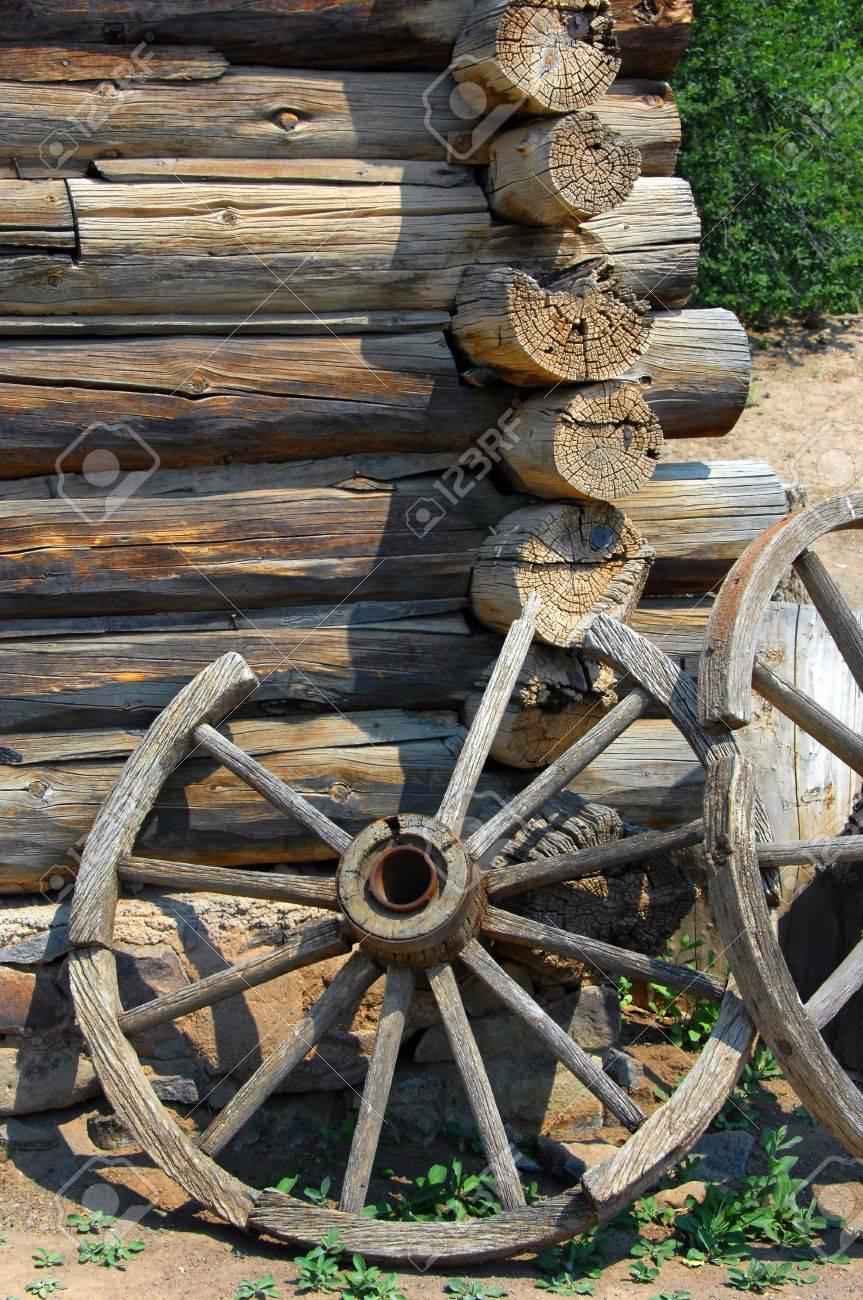 Two rustic wagon wheels lean against a log cabin wall at the El Rancho De Las Golondrinas National Historic Trail. - 15110810