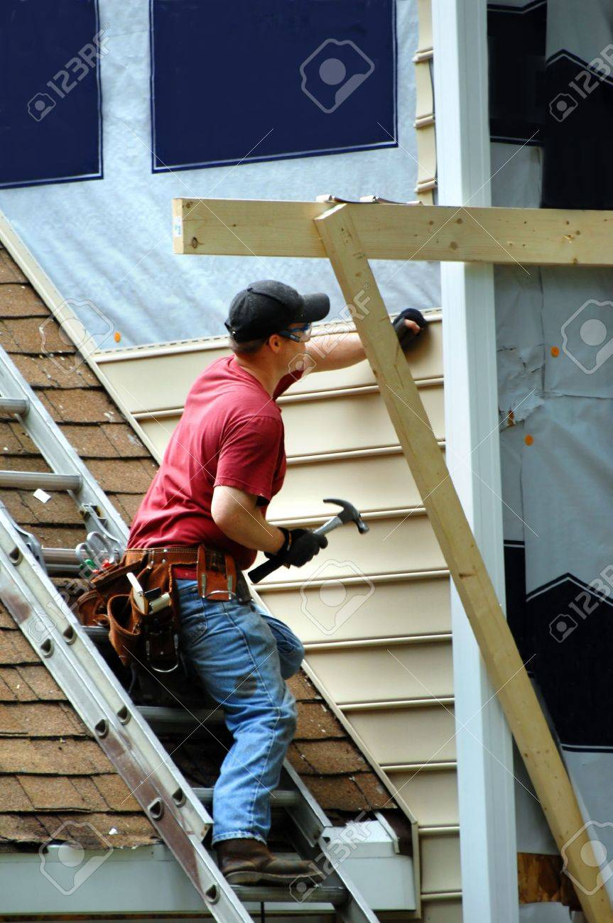 Young carpenter installs new sideing on a two story home. He is holding a hammer and nail. - 19466393
