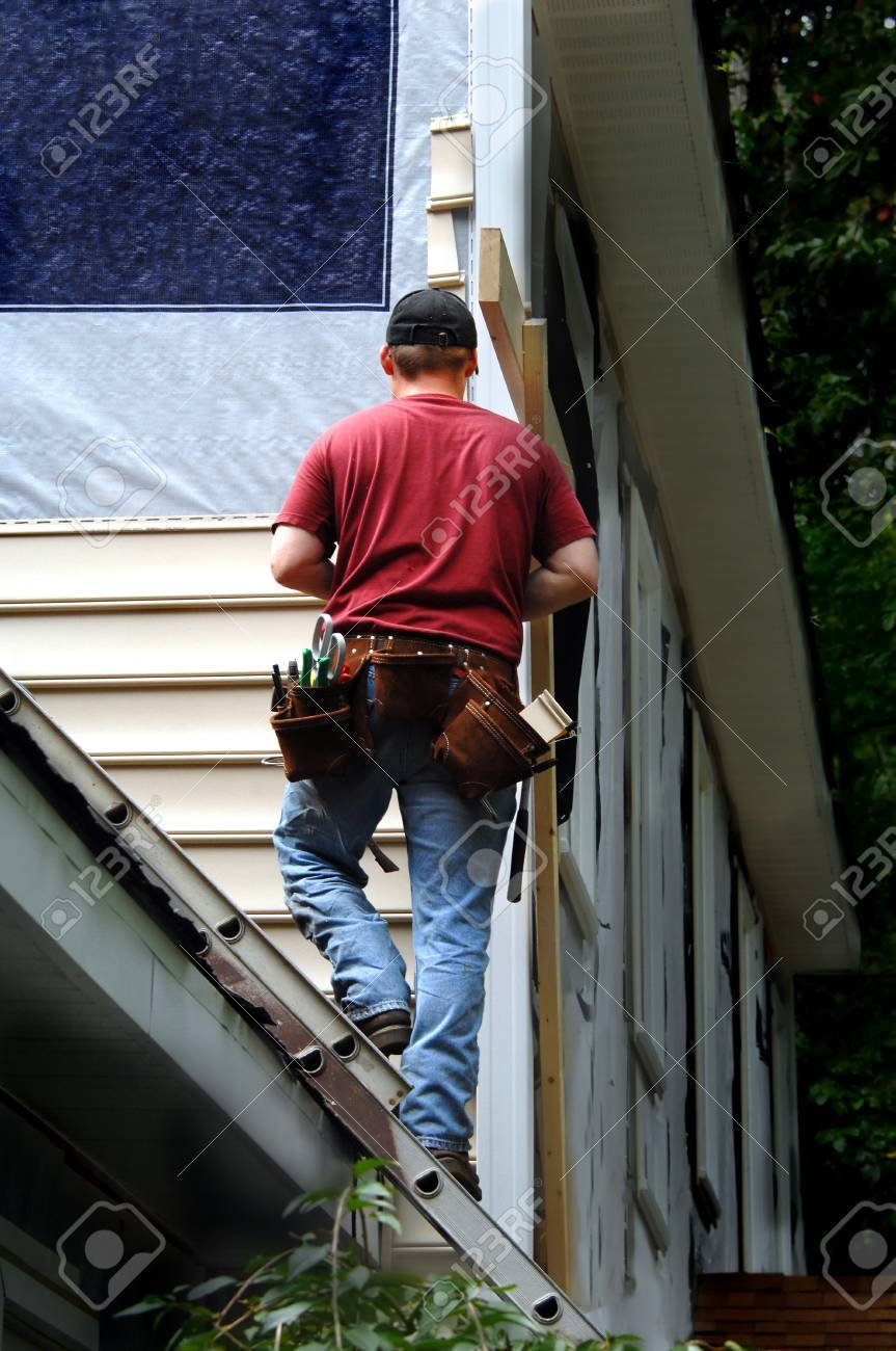Homeowner does a self installment job on his home siding. He is standing on a ladder attached to the roof of his home. - 19466566