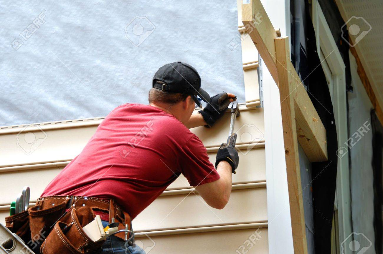 Young homeowner installs siding to his home. He is holding a hammer and wearing a tool belt. - 19466326