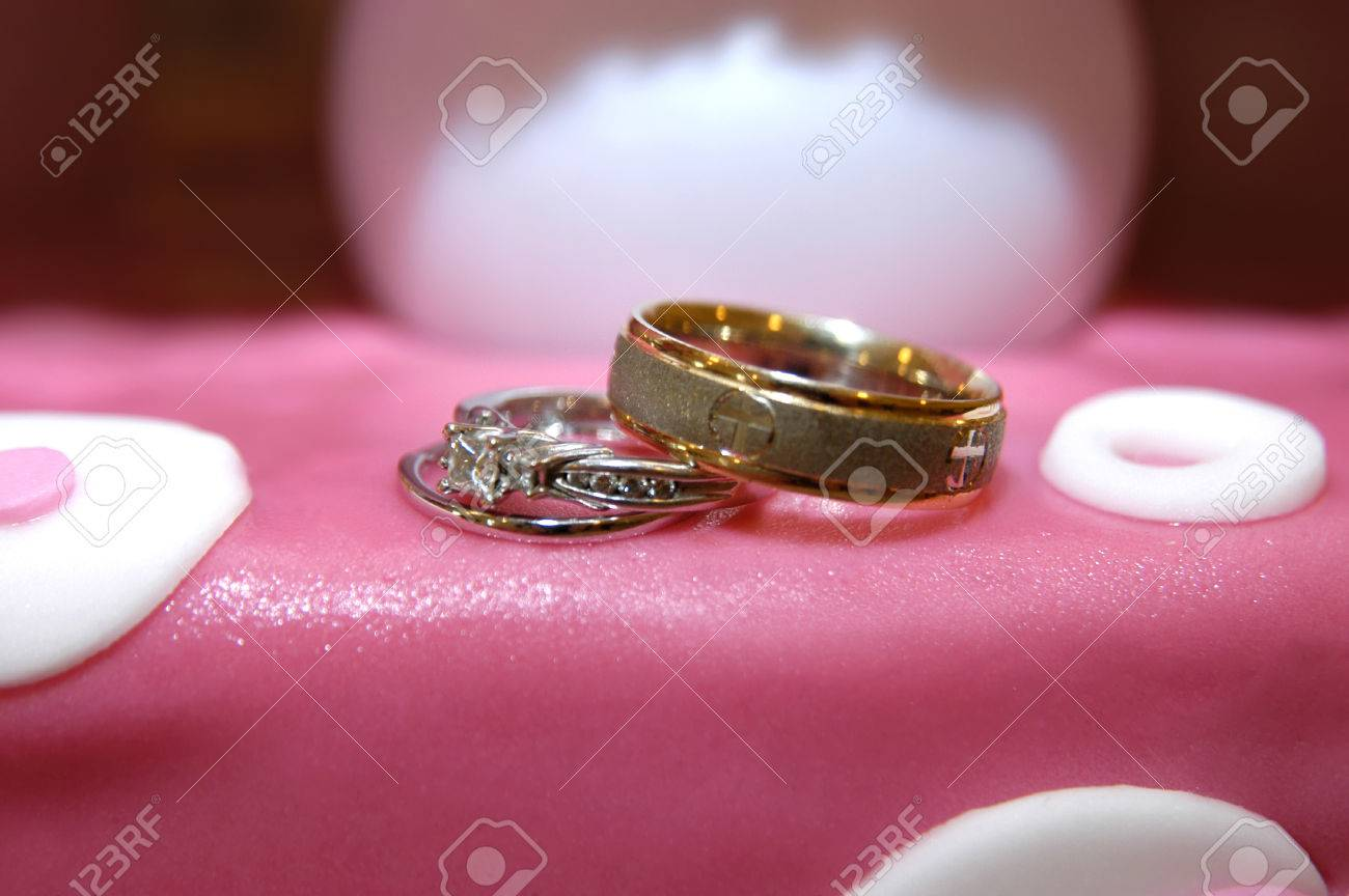 His And Her Wedding Rings Sit On Top Of Pink Fondant Frosting ...