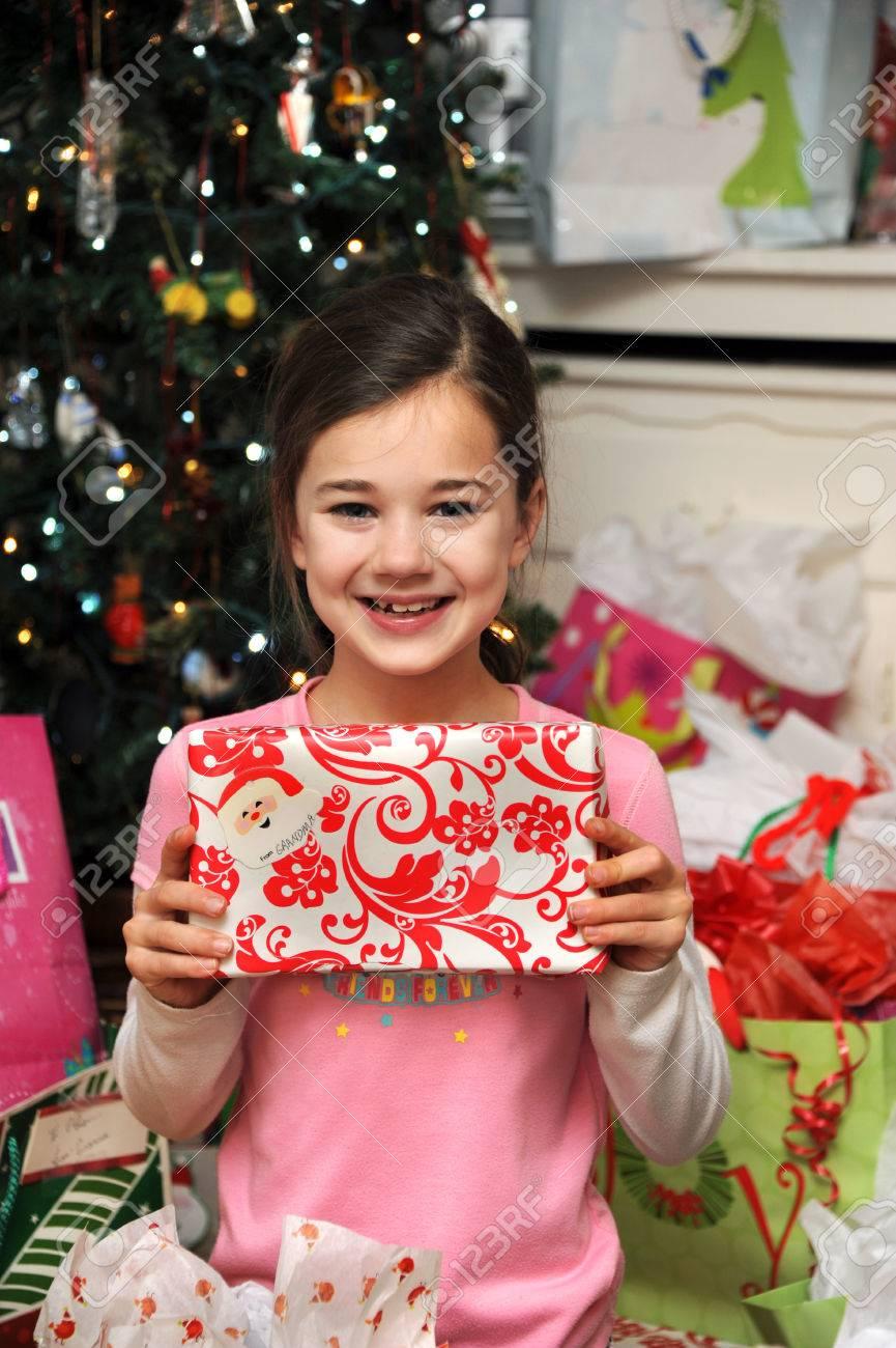 Regali Di Natale Per La Nonna.La Bambina Tiene Un Regalo Di Sua Nonna E Sorride E La Mattina Di Natale E Lei E Circondato Da Regali