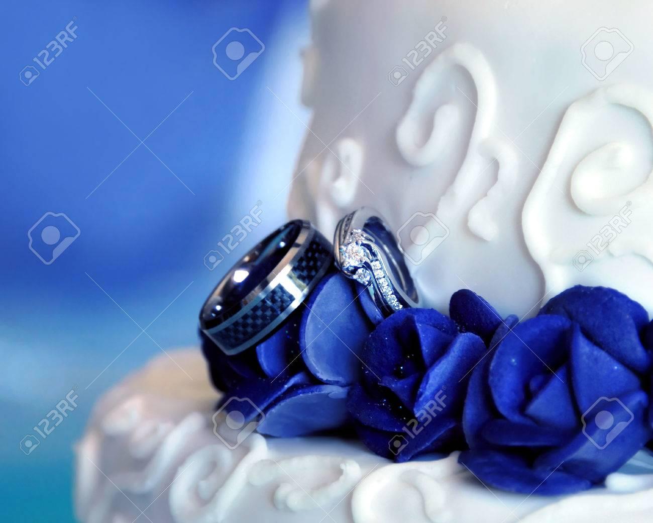 Zwei Eheringe Schmucken Unter Blauen Rosen Auf Einer Hochzeitstorte