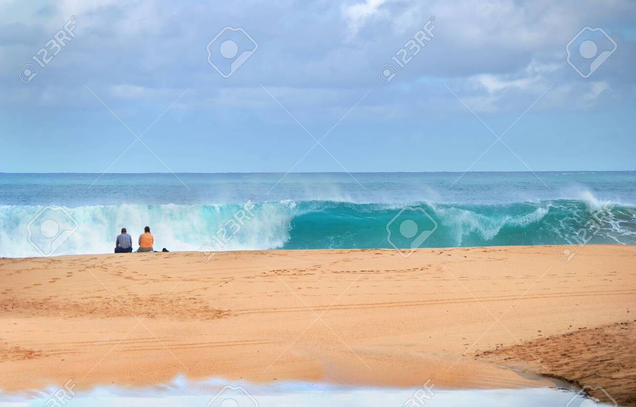 Couple sits on the beach watching the waves roll in on the Island of Kauai, Hawaii. Curling turquoise wave breaks in front of them. Water washes behind them. - 128873189