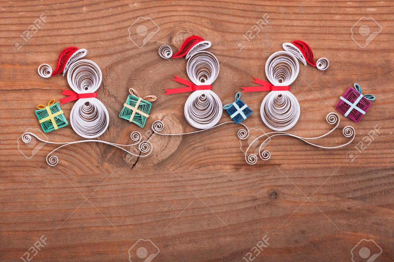 Creative Paper Christmas Card On A Wooden Background. Quilling