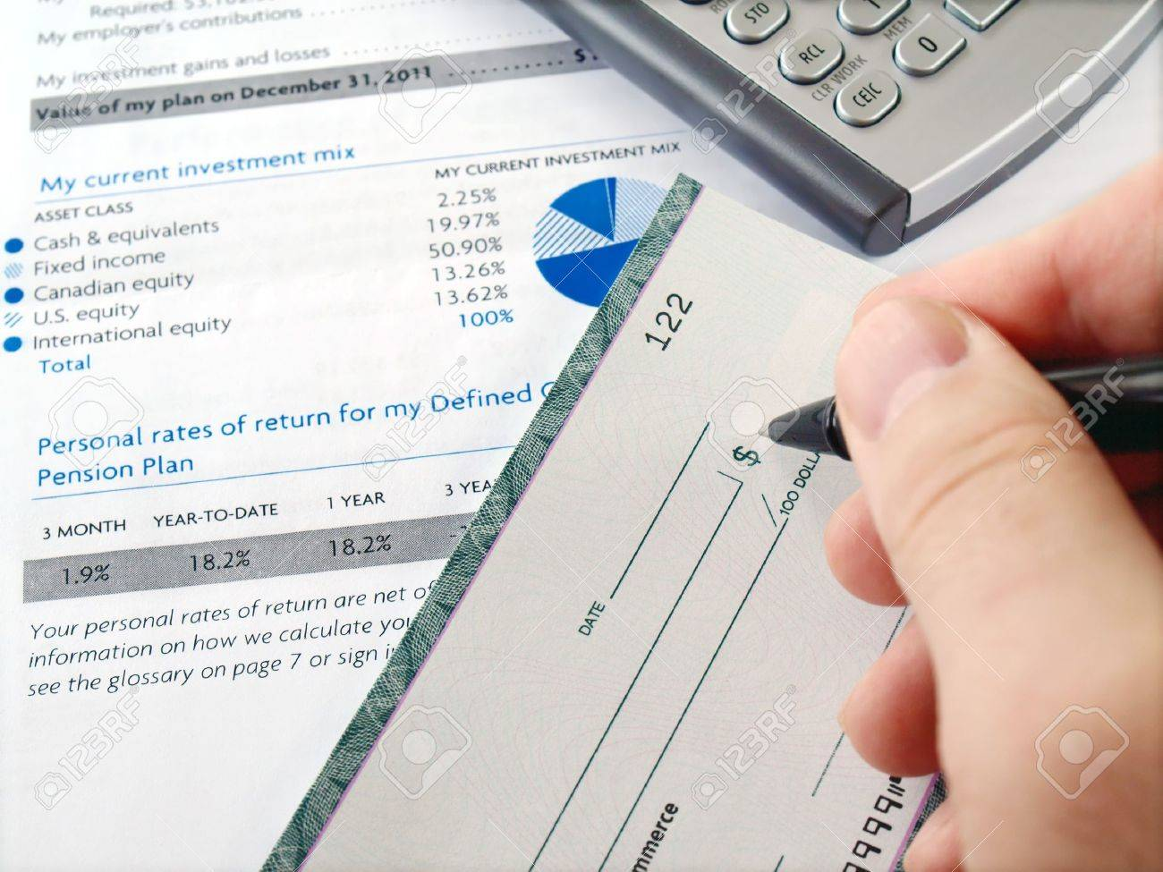 Man filling out  cheque on the investment papers Stock Photo - 9092876