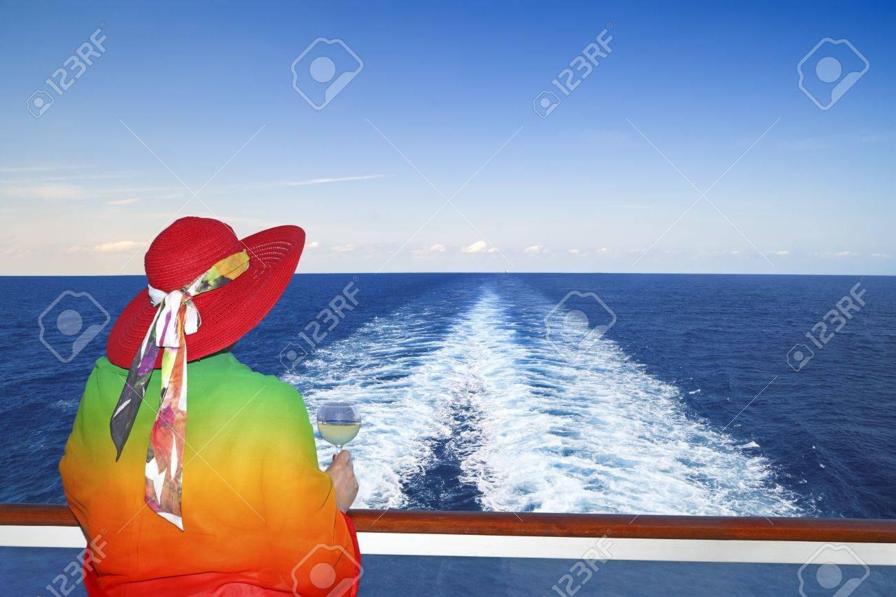 Señora con una copa de vino en un barco de crucero que mira en la estela del barco Foto de archivo - 18775461