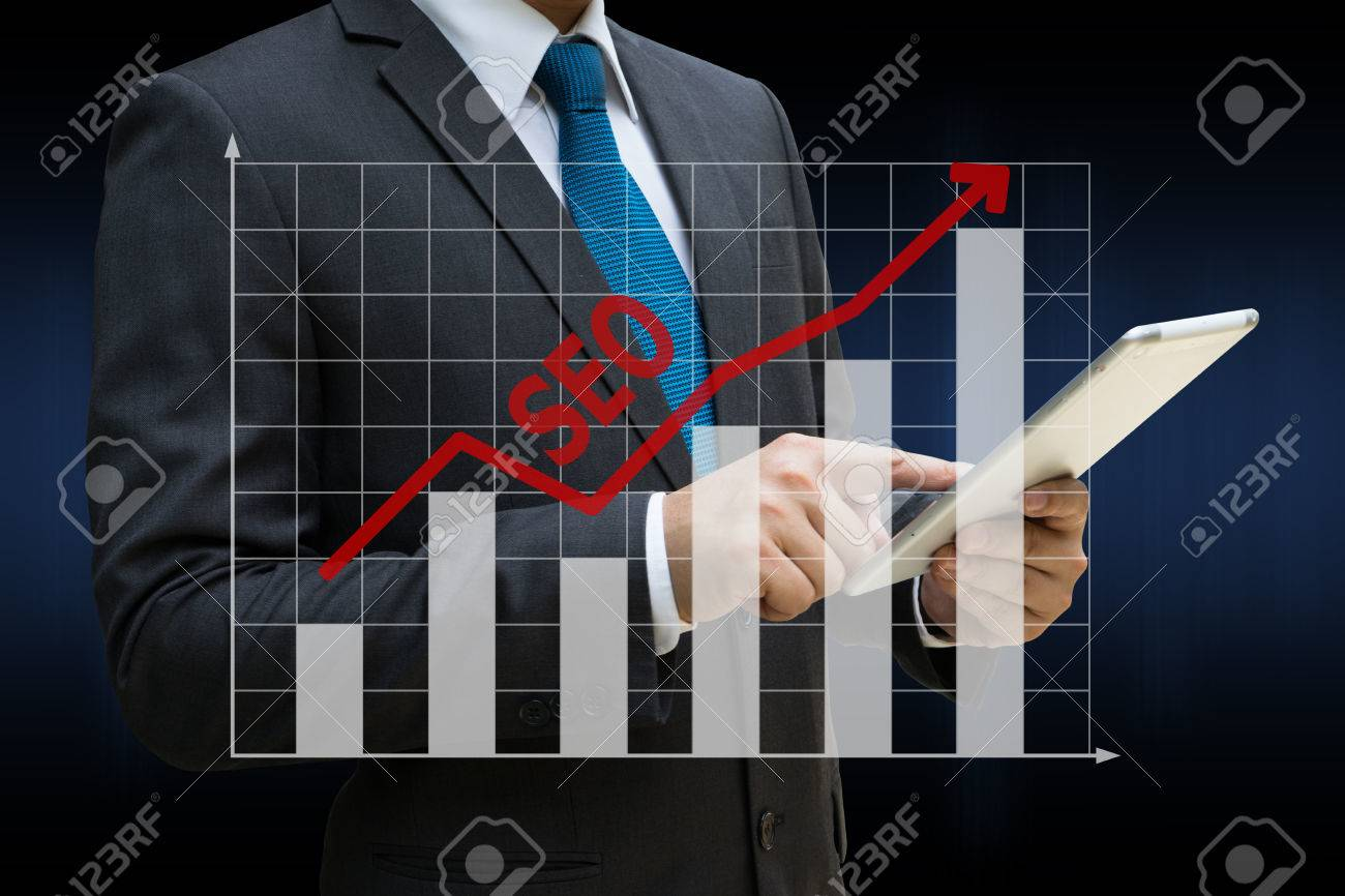 Business Man touching modern tablet with the SEO bar charts showing growing revenue on touch screen Standard-Bild - 81562516
