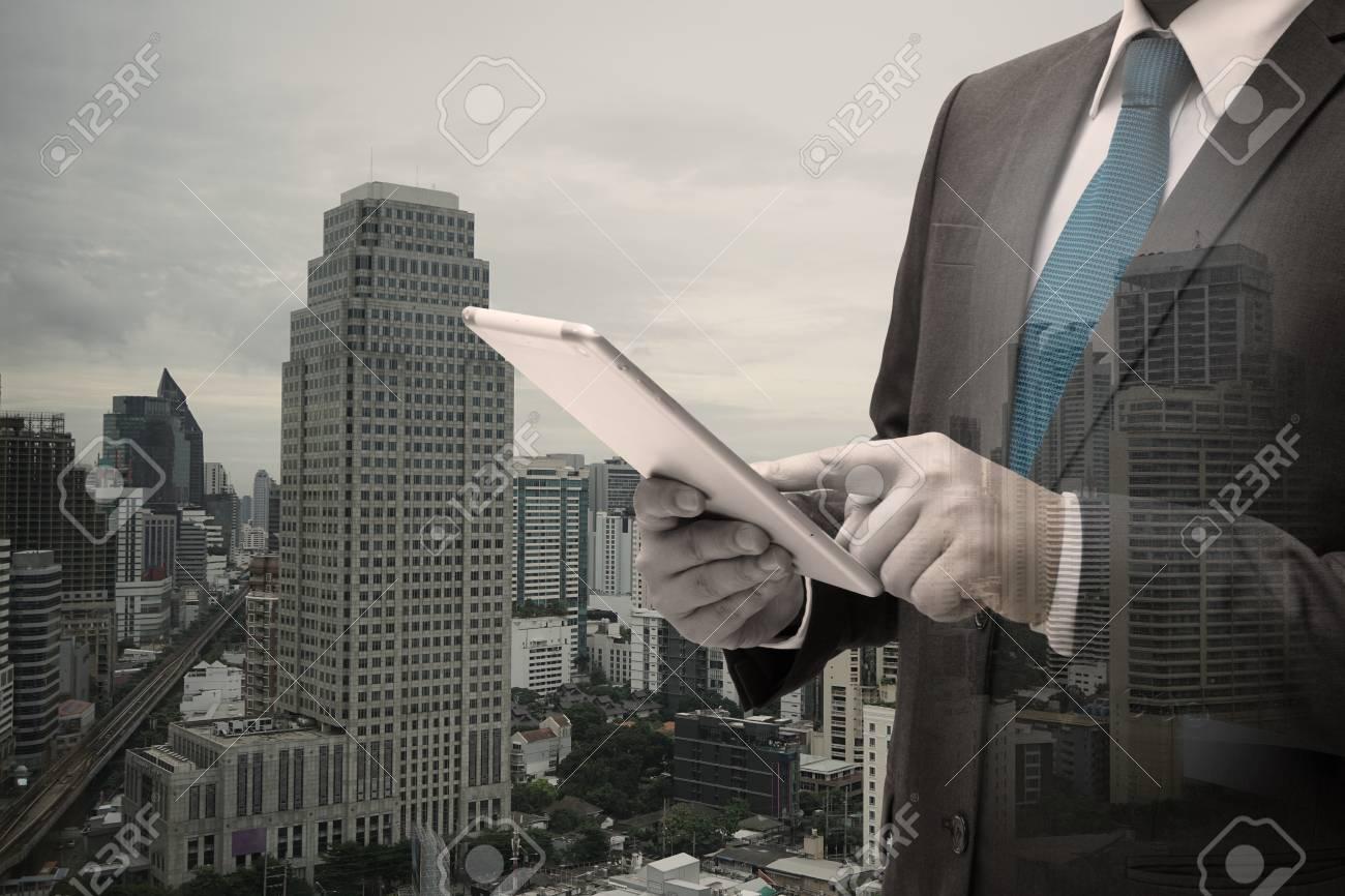 Double exposure of Businessman Using Digital Tablet Standard-Bild - 83670935
