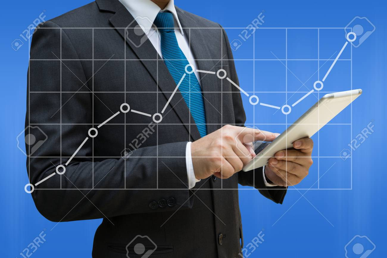 Business Man touching modern tablet with the line charts showing growing revenue on touch screen Standard-Bild - 90179730