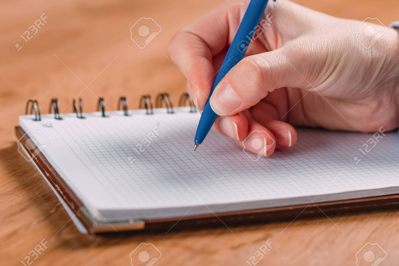Close up of woman's hands writing in spiral notepad placed on wooden desktop - 135273150