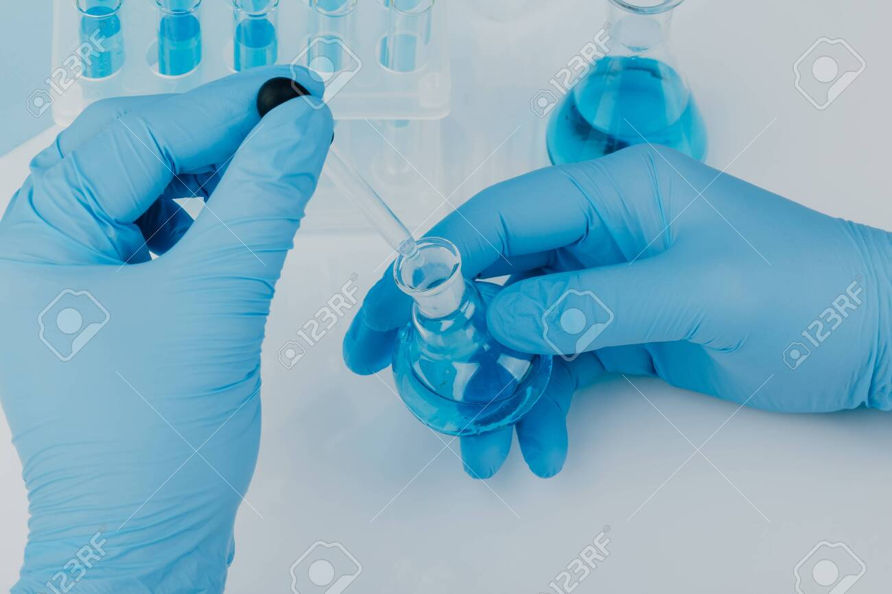 Laboratory glassware with test tubes. scientific laboratory equipment. hands of a scientific researcher in blue gloves - 147504153