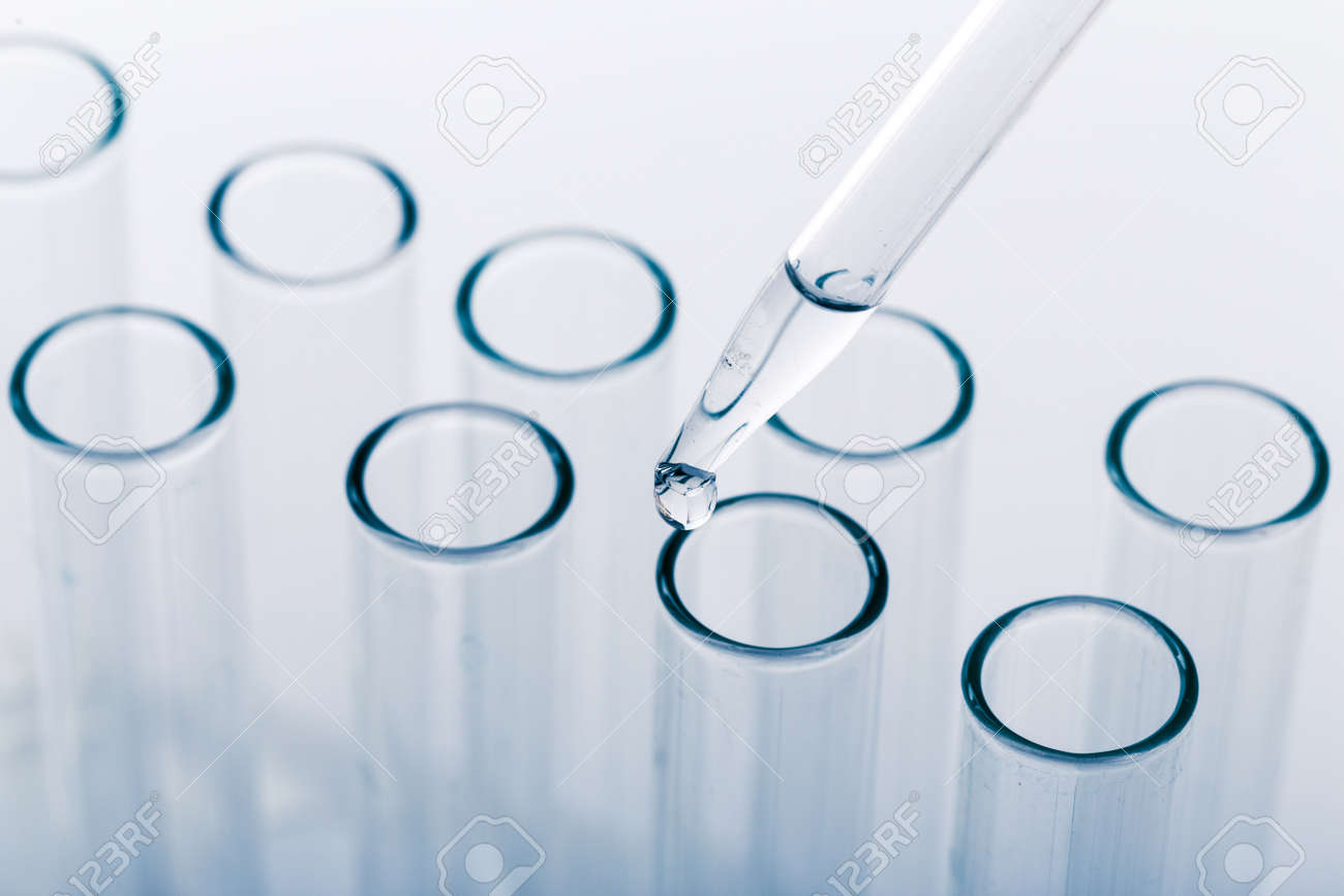 pipette with a drop and scientific laboratory test tubes in a research laboratory. study of a virus or vaccination. - 151202587
