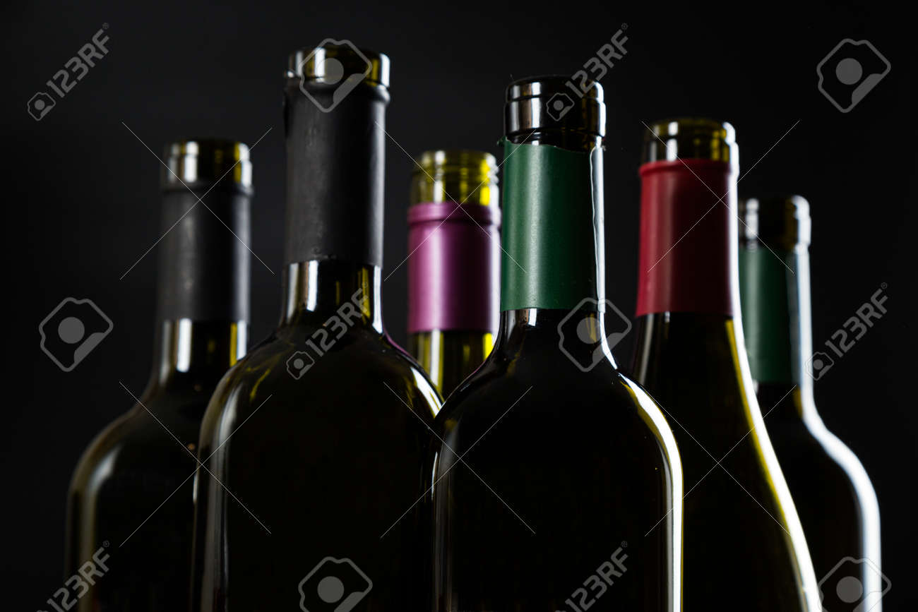 several open Bottles of wine are in a row on a dark glossy background. - 165422373