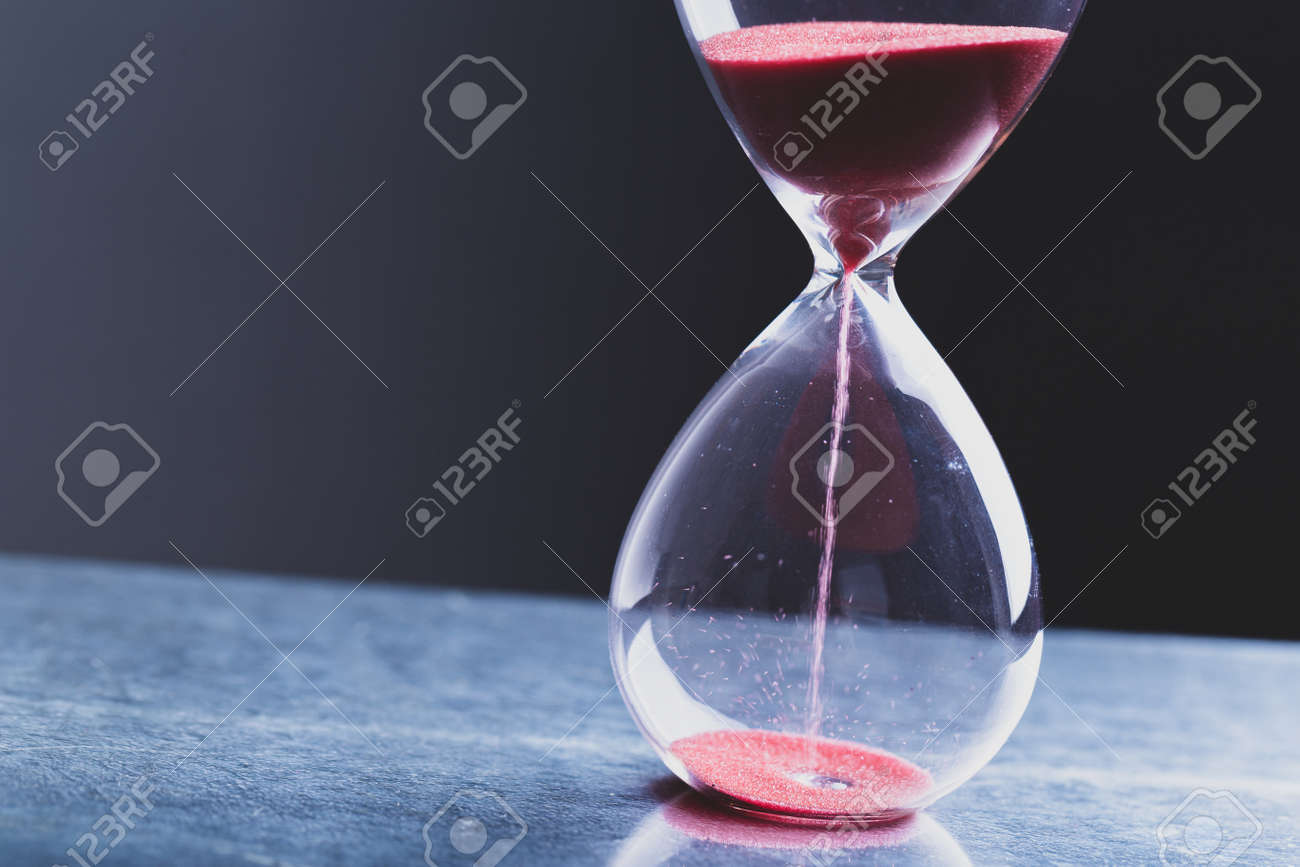 Hourglass as a concept of passing time for business deadline, urgency and outcome of time. - 166365441