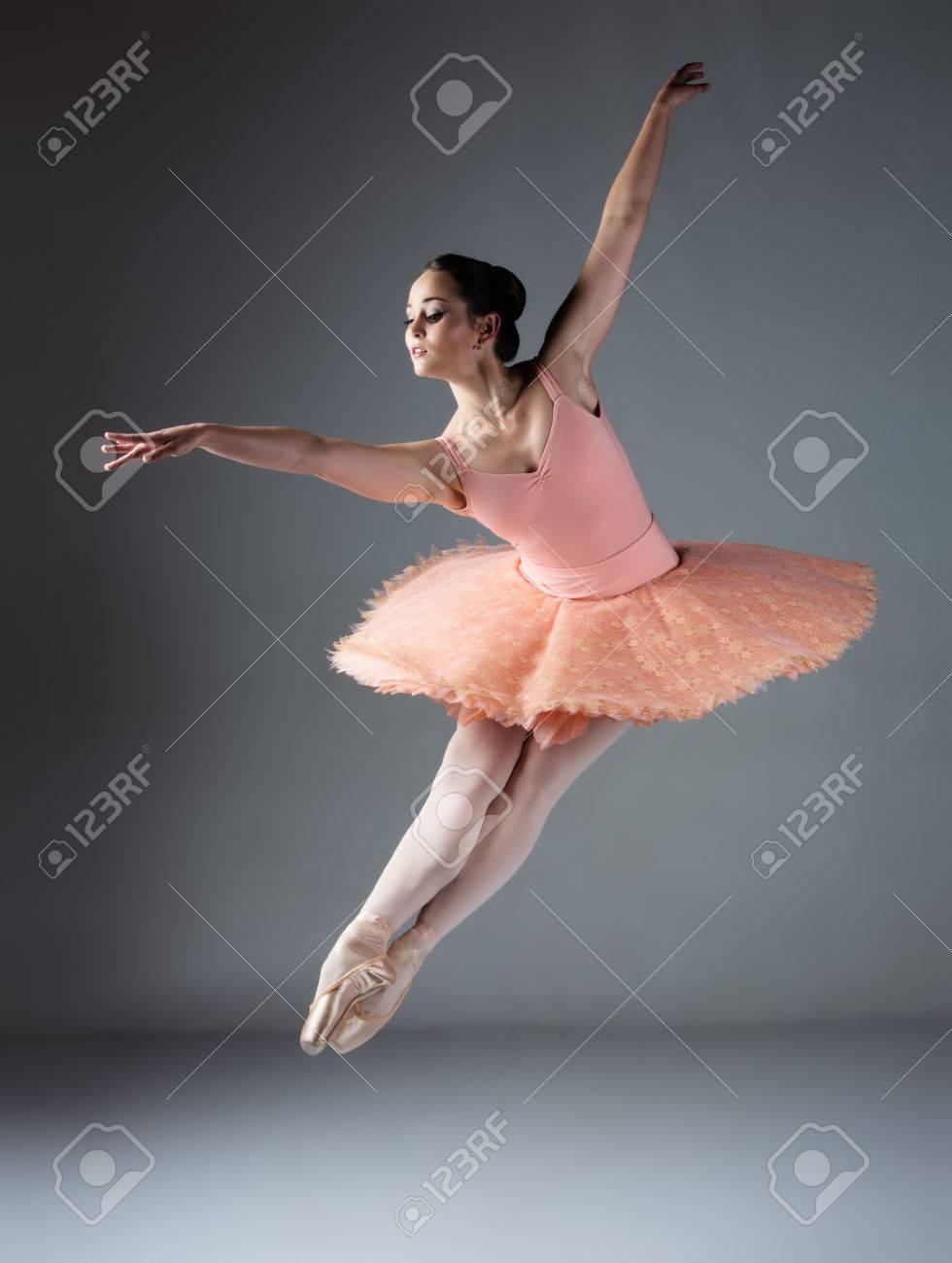 Hermosa bailarina de ballet femenino sobre un fondo gris. Bailarina lleva un tutú de color naranja, rosa y medias pointe zapatos.