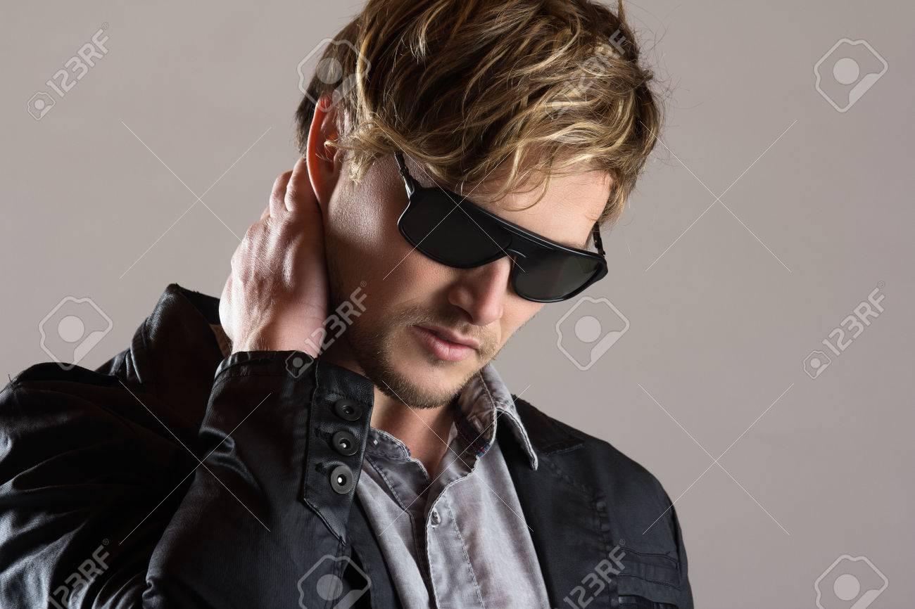 acheter authentique outlet à vendre prix de la rue Portrait d'un homme blond, caucasien, beau porter un bouton chemise bleu  délavé, veste noire en cuir et lunettes de soleil.