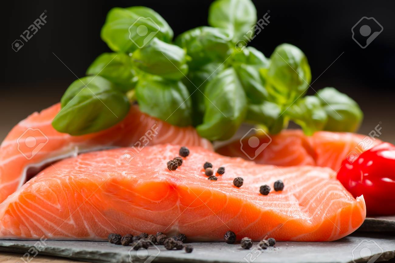 Fresh salmon fillet with basil and pepper on flat rocks Stock Photo - 17560618