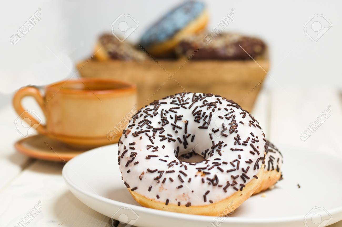 white donut with chocolate sprinkles cup of tea and wooden box