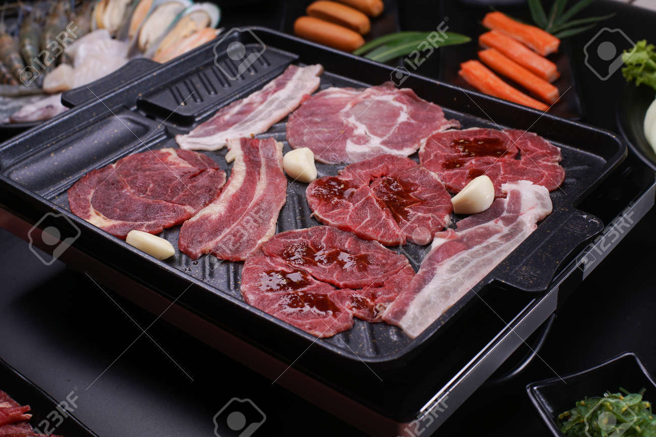 Raw beef slice for barbecue japanese style, yakiniku. Meats are being cooked on stove in a japanese restaurant. - 157190327