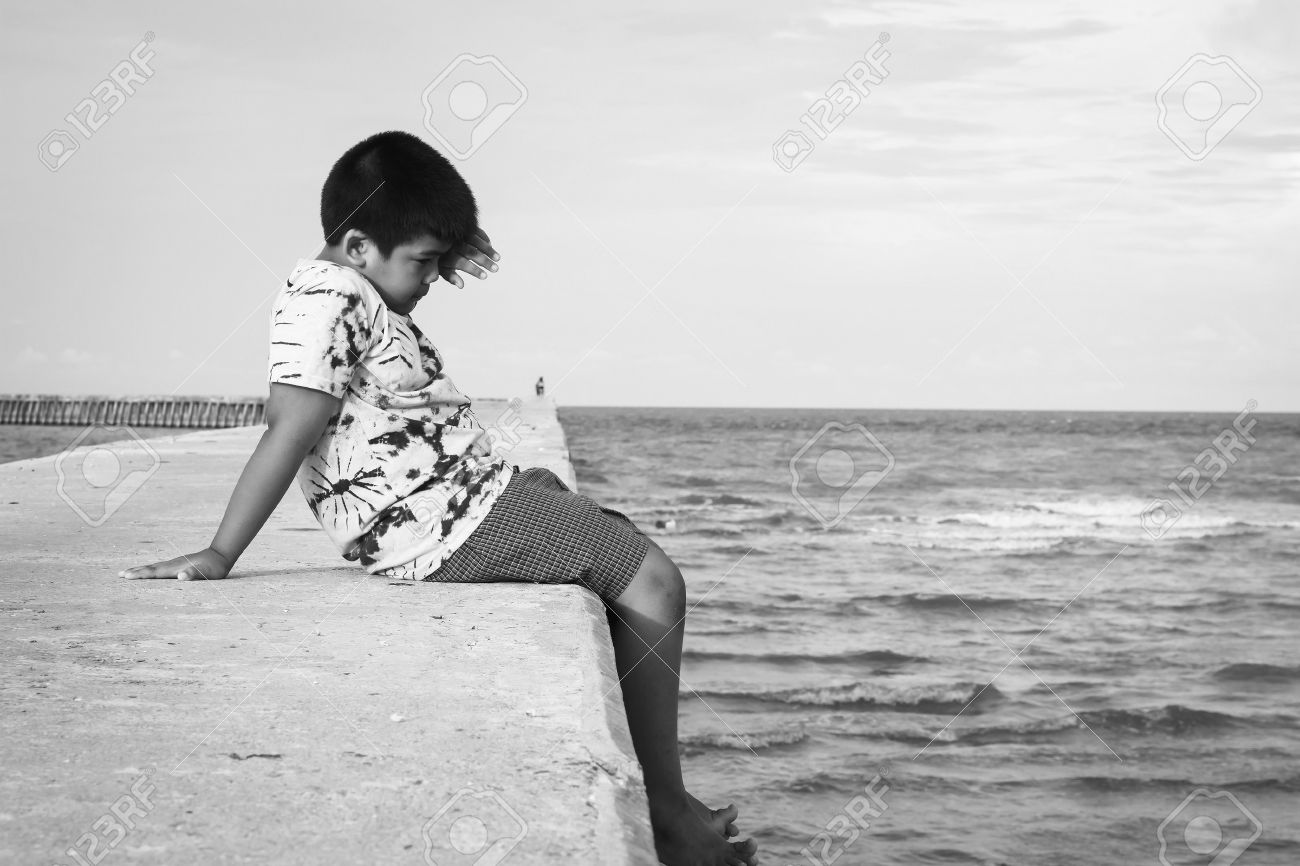cute little boy sitting alone on walkway at sea stock photo picture