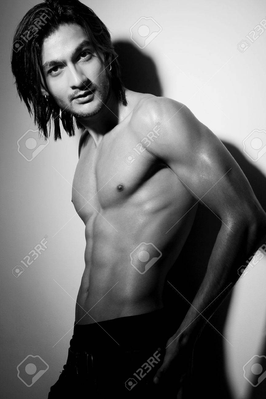 Portrait shot of a shirtless attractive young Indian man with long hair posing with hand on hip. Stock Photo - 11990347