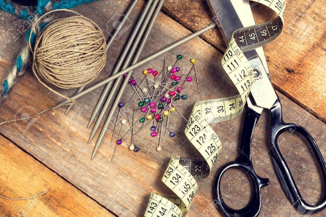 Sewing kit. Scissors, bobbins with thread, measure tape and needles on top of the old wooden table. - 36061473