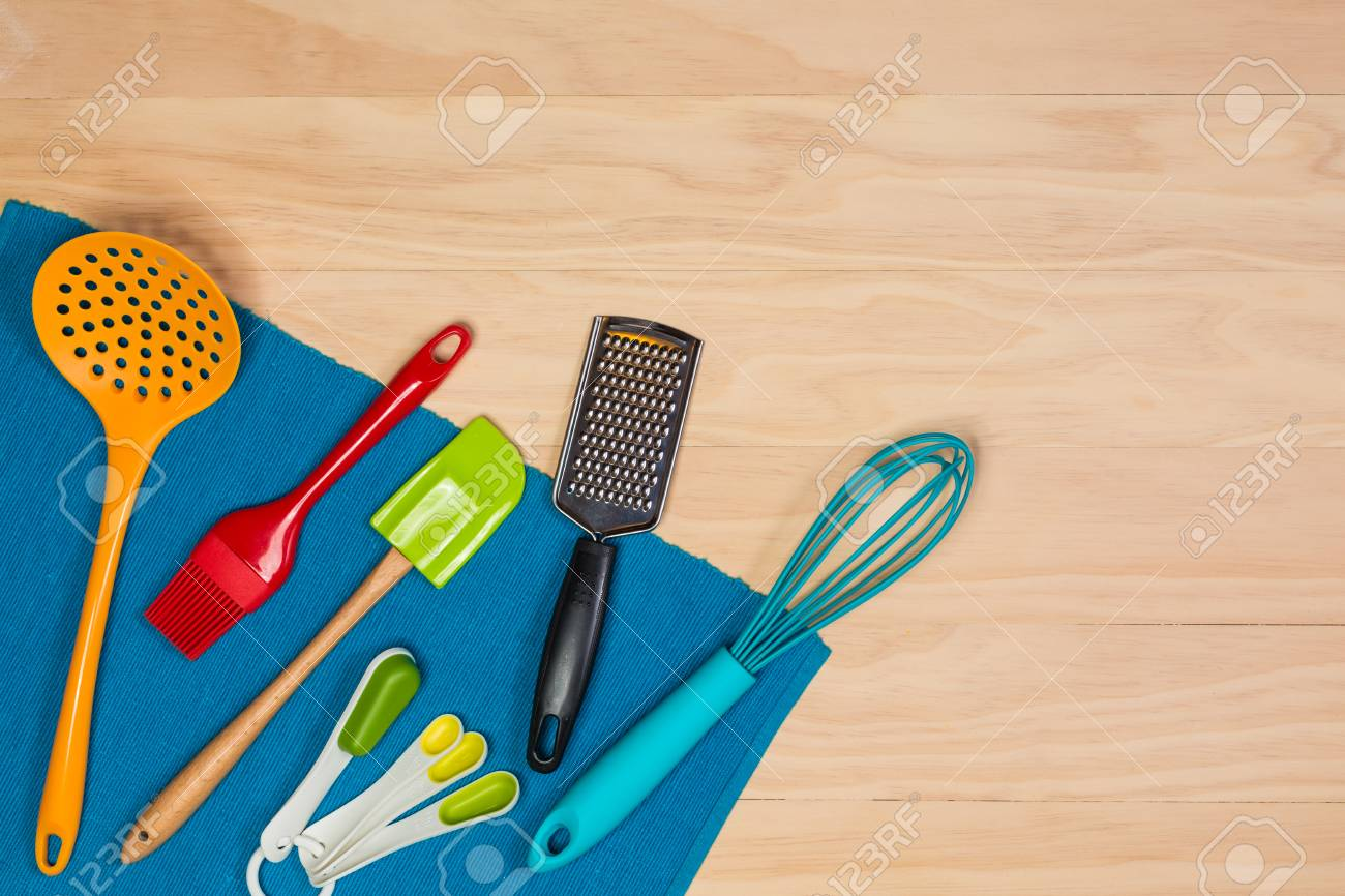 colorful kitchen utensils on wooden background