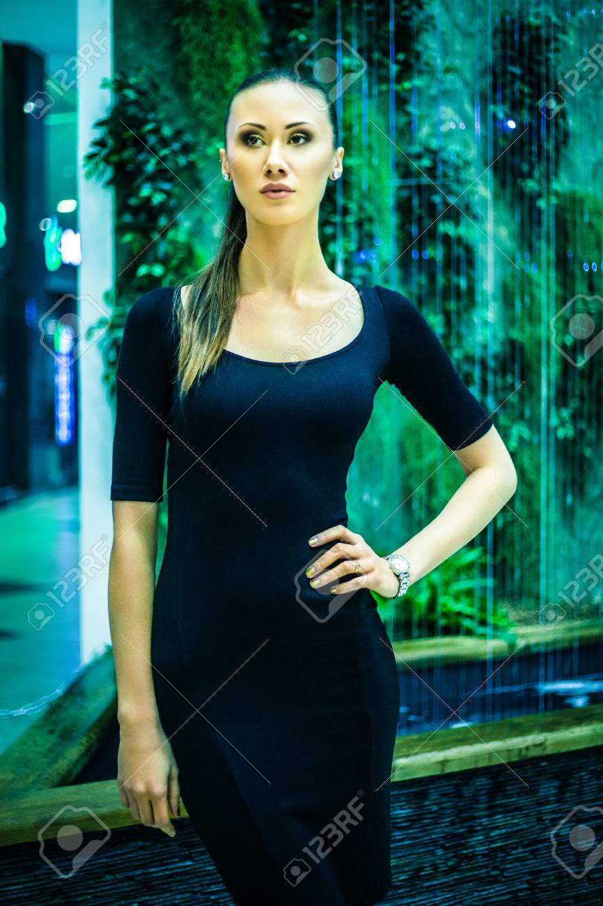 e7ecb043d11 Young beautiful stylish girl walking and posing in short black dress in  city Stock Photo -