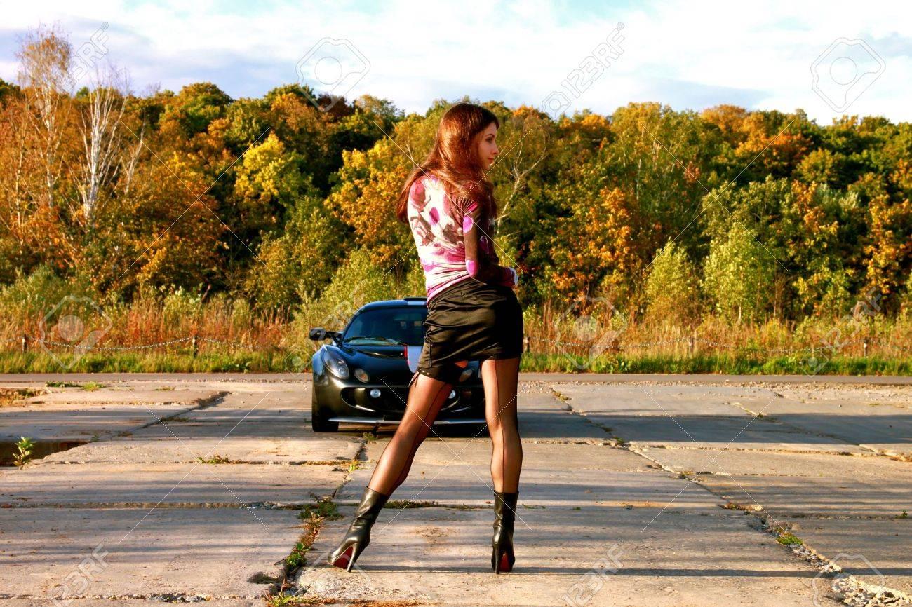 Sexy belle fille près de voiture de sport sur route. Automne.  Banque d'images - 7891223