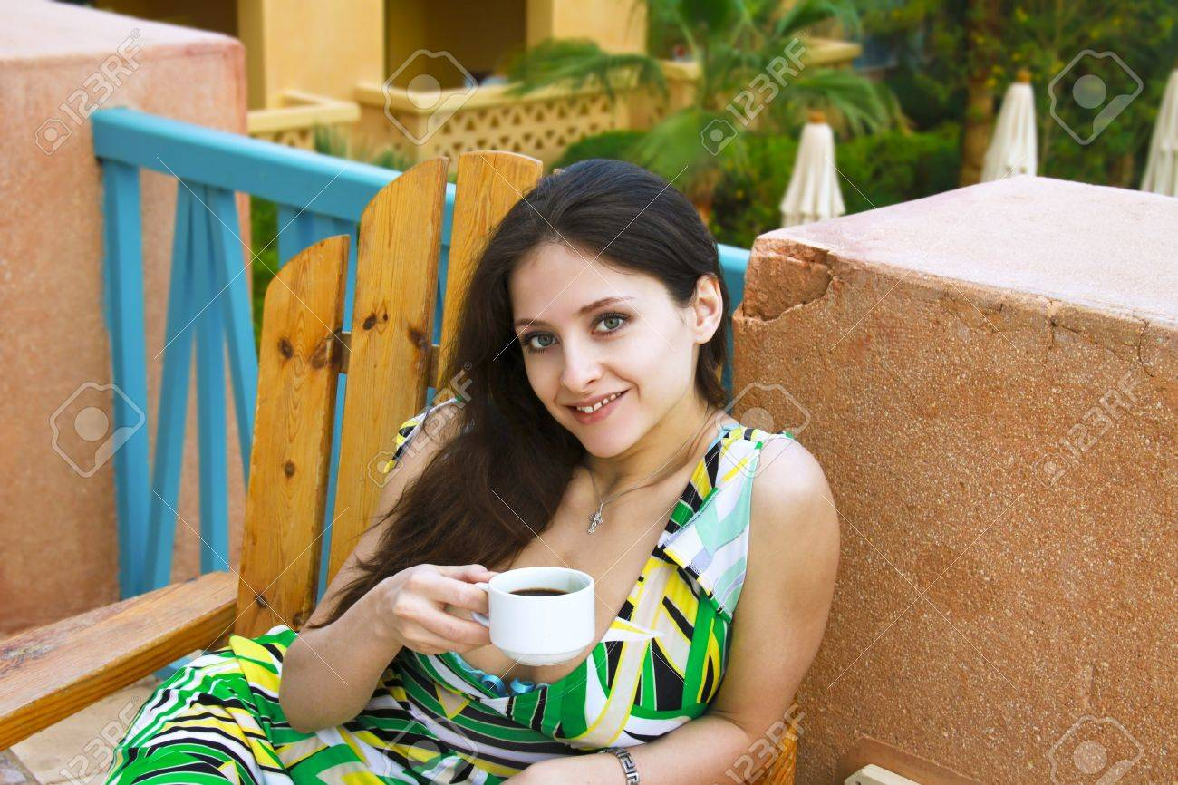Beautiful girl in green dress is drinking coffee outdoor with smile Stock Photo - 8764169