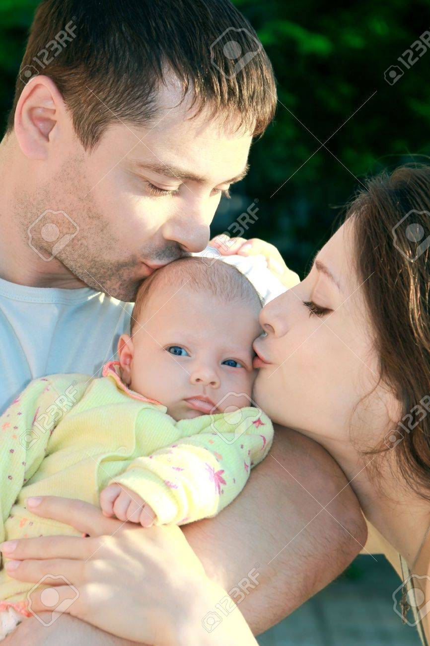 Parents kissing beautiful blue eyes baby girl on nature. Babe looking serious and thinking about. Happy family Stock Photo - 10365861