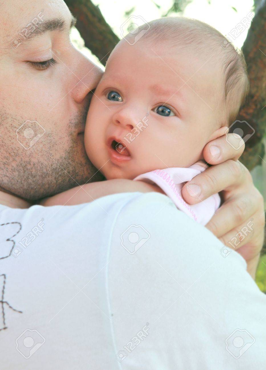 Father kissing little baby girl on the hands on nature background Stock Photo - 10769493