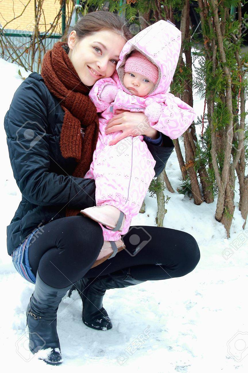 Beautiful young mother holding little baby girl on winter background. Portrait of happy family Stock Photo - 12614927