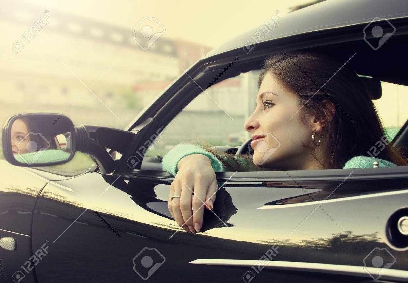 Beautiful smiling girl sitting in new sport car and looking from window Stock Photo - 14019853